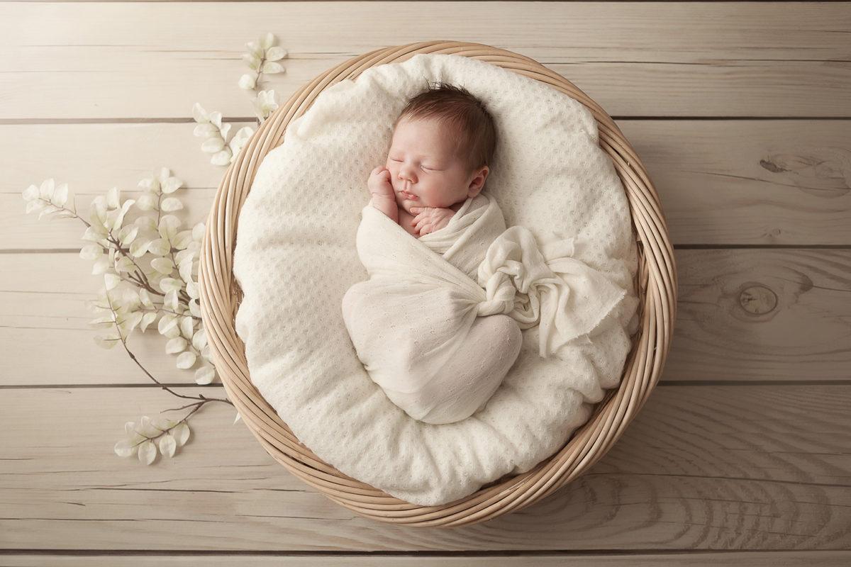 séance photo nouveau-né dans un panier en osier couleurs naturelles et douces