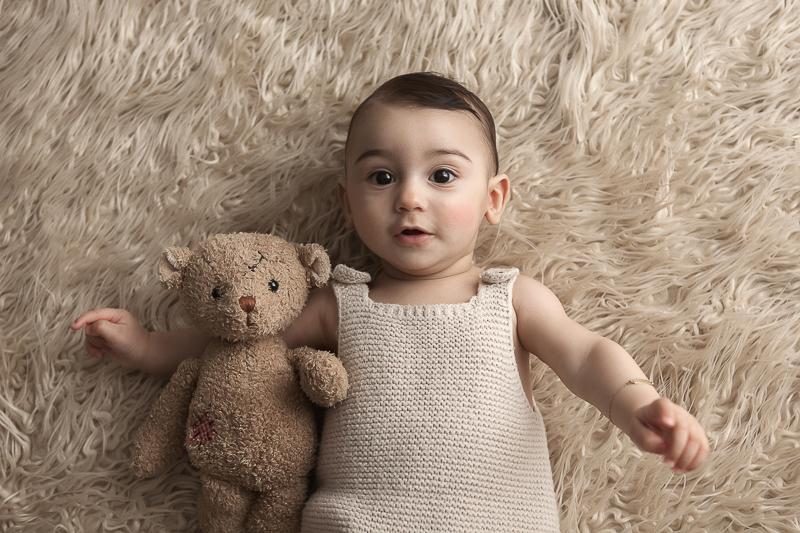 bébé de 6 mois allongé sur le dos sur une fourrure avec son ours en peluche dans son bras