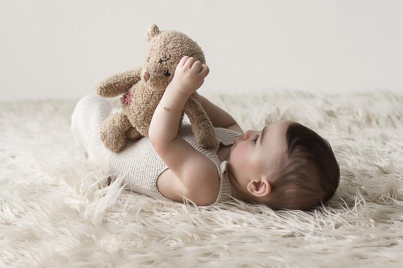 bébé allongé sur le dos bras tendu joue avec son ours en peluche dans les mains